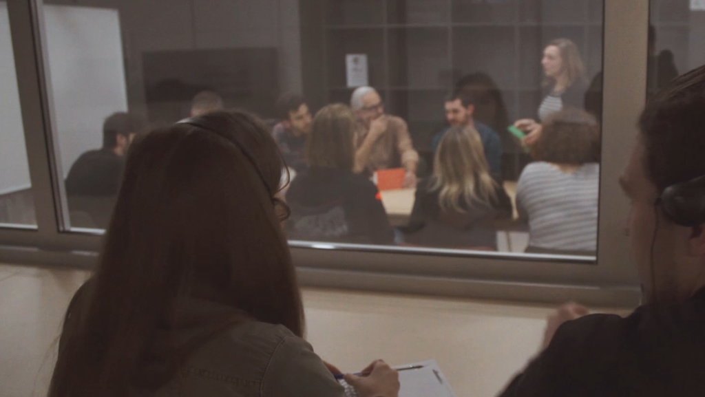 People participating in a focus group while two members of Food for Tomorrow are taking notes behind the spy glass.